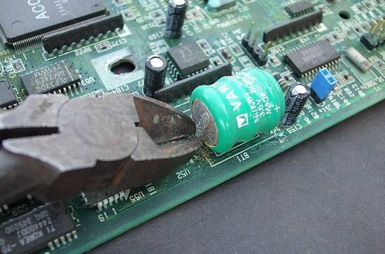 Snipping the old CMOS battery from the motherboard